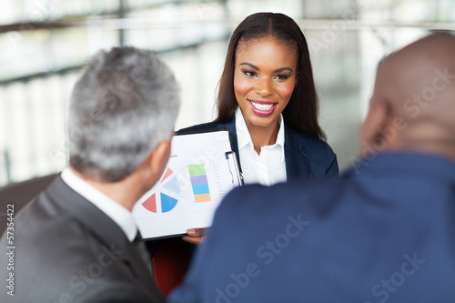 young african businesswoman explaining graph to business team