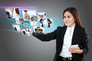 Businesswoman holding smartphone and using digital touchscreen t