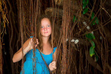 Teen-girl in a blue dress in mangrove forest.