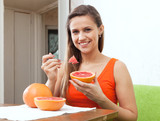 woman eats grapefruit with spoon