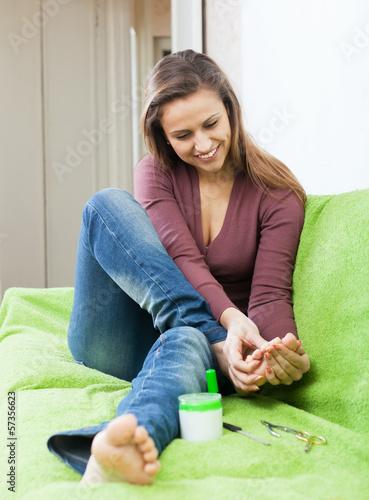 Happy beauty woman looks at her toenails