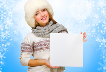 Girl with empty card on winter background