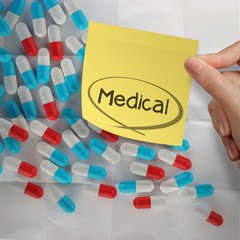hand holding sticky note medical with Pills spilling on crumpled