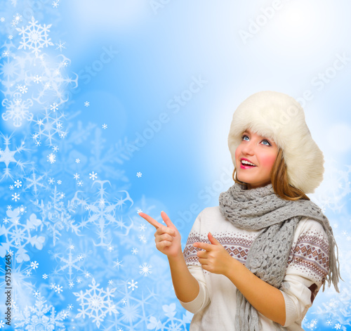 Girl shows pointing gesture on winter background