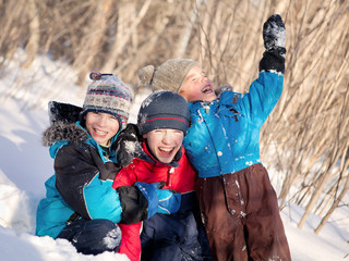 children in winterwear laughing while playing in snowdrift