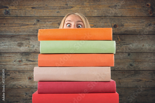 woman with big eyes looking for stack of books