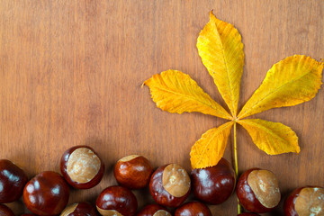 chestnuts with leaf on wooden board