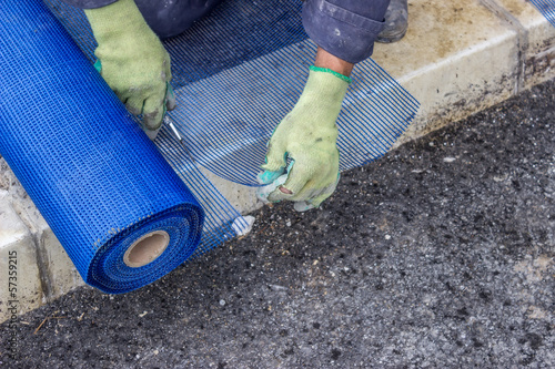 building worker cutting plastic grid