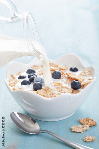 milk pouring onto cornflakes with blueberry