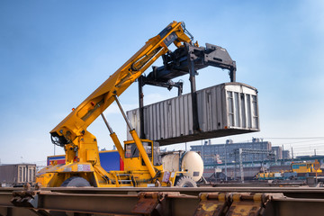 Crane lifts a container loading a train