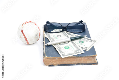 old books with eye glasses and money and ball