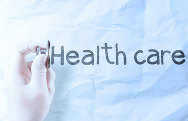 Stethoscope in hand with health and crumpled paper background ca