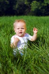 Little girl sitting on a green grass