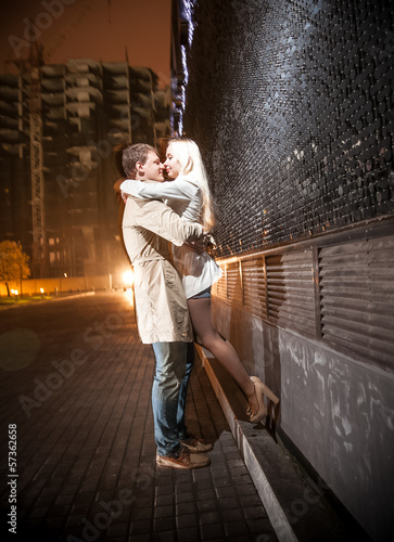young couple kissing at evening near black wall