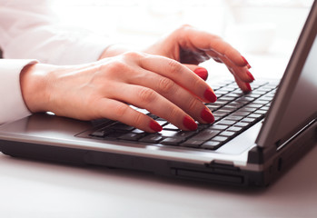 female is typing on keyboard.