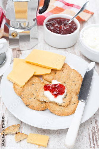 Breakfast with crackers, cheese, cream and berry jam