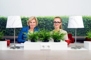 Confident Female Environmentalists Sitting At Desk