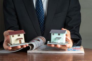 住宅を販売するスーツの営業マン