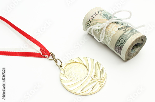 Gold medal and roll of tied banknotes on white background
