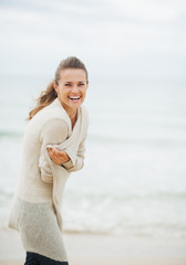Happy young woman in sweater on coldly beach