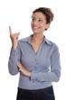Lachende isoliert junge Frau zeigt mit dem Zeigefinger auf etwas