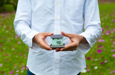 白いシャツの男性が自然の中で家のミニチュアを持っている