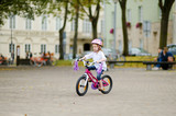Little girl riding a bike in a city