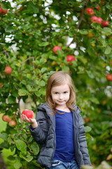 Little girl with an apple by an apple tree