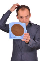 Man checking his hair loss in the mirror