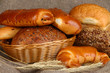 Baked bread in wicker basket on burlap background