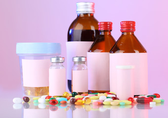 Pills and medicine bottles on pink background