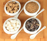 Different types of sugar in bowls on table close-up