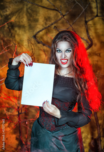 Halloween vampire holding sheet of paper