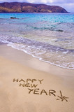 Happy new year and exclamation point written in the sand