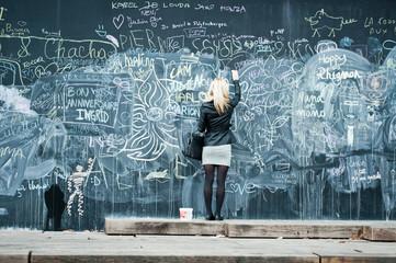 jeune femme écrinvant sur un grand  tableau