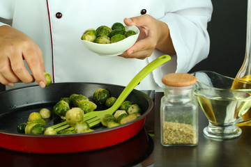 Chef prepares frresh brussels sprouts in pan