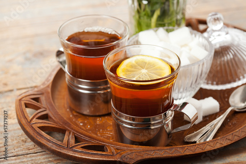 Set of cups with black tea on tray