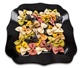 Multi-colored curly Italian pasta on a black plate