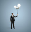 businessman holding bulbs