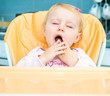 one year old girl in a highchair for feeding
