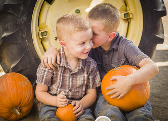 Two Boys Sit Against Tractor Tire Holding Pumpkins Whispering
