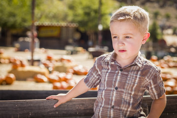 Little Boy Standing Against Old Wood Wagon at Pumpkin Patch.