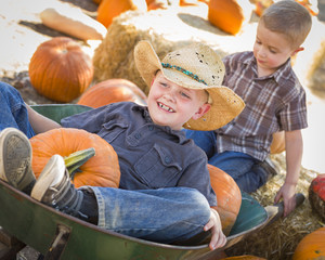 Two Little Boys Playing in Wheelbarrow at the Pumpkin Patch.