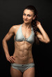 Young fitness woman posing over black