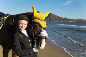Young girl with a favorite horse on the beach.