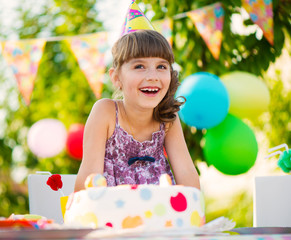 Pretty girl with cake at birthday party