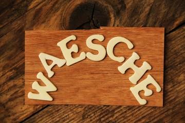 das Wort WAESCHE auf Holztafel