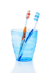 toothbrushes in blue plastic glass