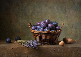 Still life with black plums in a basket on the table