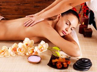 Masseur doing massage on woman body in spa salon